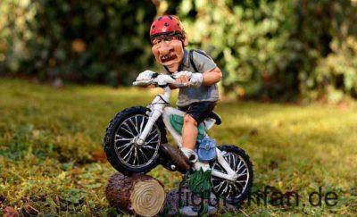 Mountainbiker auf seinem Mountainbike mit rotem Helm fährt über einen Baumstamm