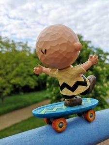 Peanuts Figur von Charlie Brown recht unsicher auf einem Skateboard