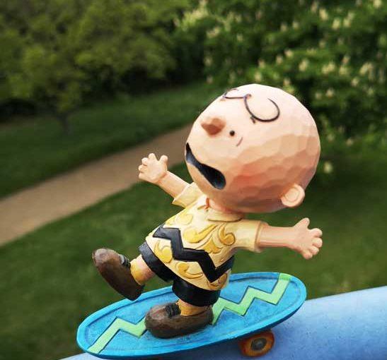Die Figur Charlie Brown von den Peanuts auf einem Skateboard