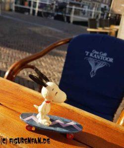 Peanuts Figur Snoopy auf seinem Skateboard auf einem Tisch