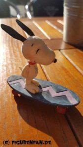 Peanuts Figur Snoopy fährt Skateboard auf dem Tisch