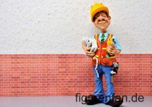 Architekt Figur Funny Job vor Wand mit Messinstrument und Plänen