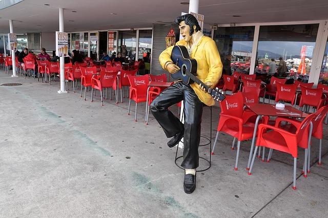 Lebensgrosse Elvis Figur mit schwarzer Akustik Gitarre vor einem Restaurant
