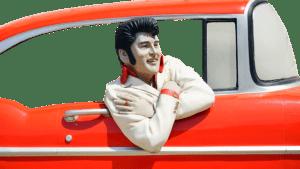 Elvis Figur schaut aus einem roten Auto