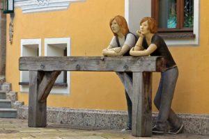 Zwei lebensgrosse Figuren lehen am Balken