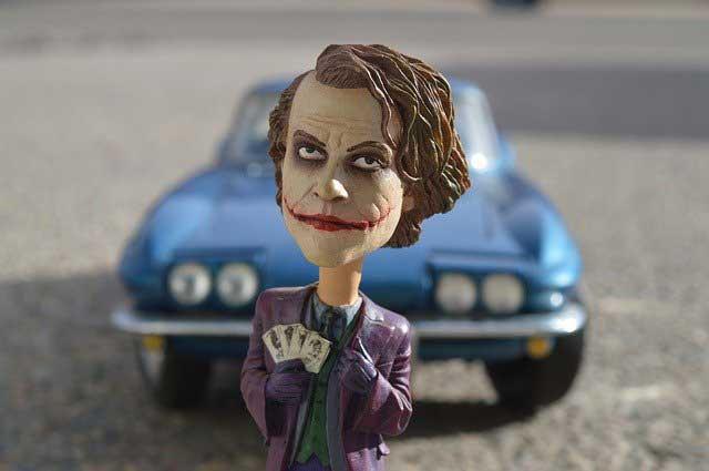 Joker Actionfigur vor Sportwagen
